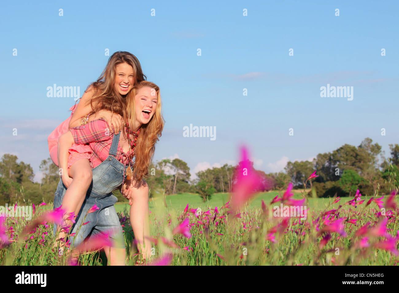 Sonriente, feliz primavera o verano piggy back adolescentes o adolescentes niños Imagen De Stock