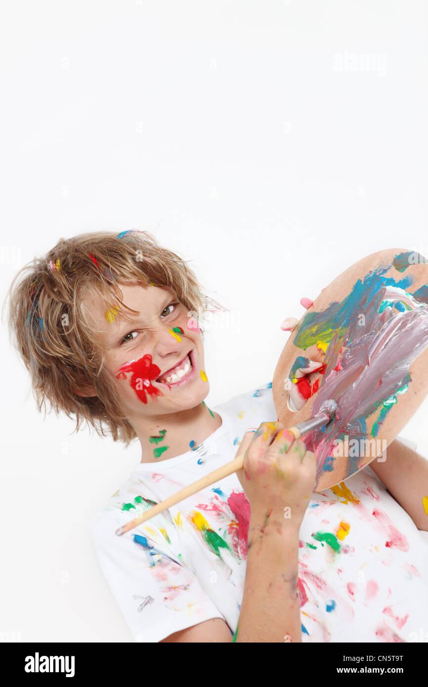 Impertinente kid jugando con paint Imagen De Stock