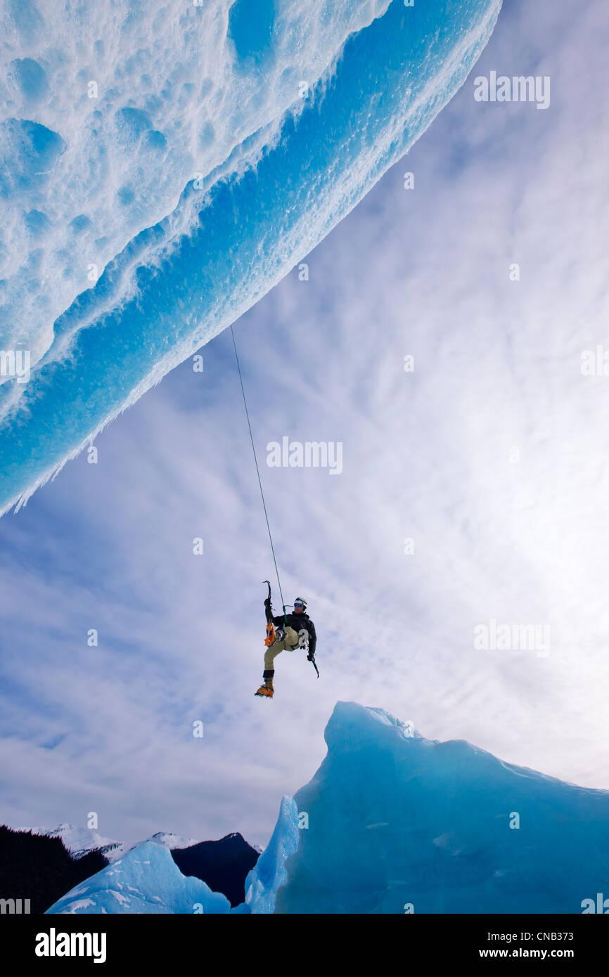 Un escalador de hielo bascula hacia abajo de la cuerda para llegar frente a un enorme iceberg congelado en Lago Imagen De Stock