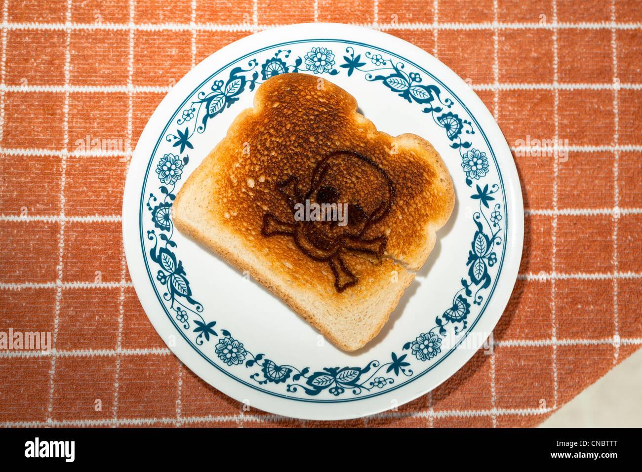 Cráneo y huesos cruzados grabada en un trozo de pan tostado en un plato alergia al gluten la enfermedad celíaca. Imagen De Stock