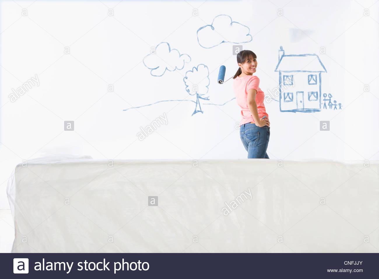 Mujer sonriente de pie en frente de la casa y familia pintados en la pared sala Imagen De Stock