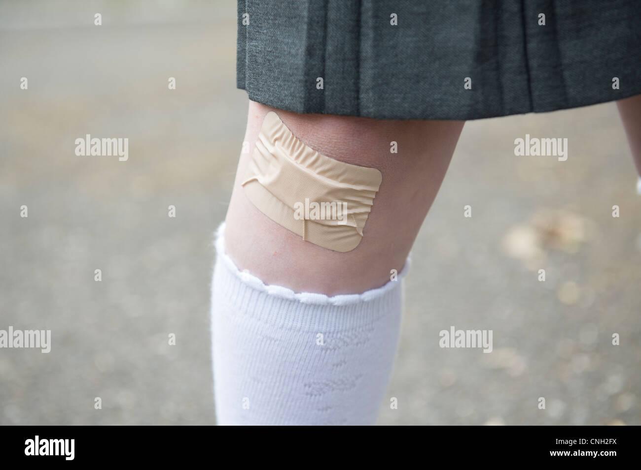 La alumna de la rodilla con un yeso pegada sobre un corte. Foto de stock