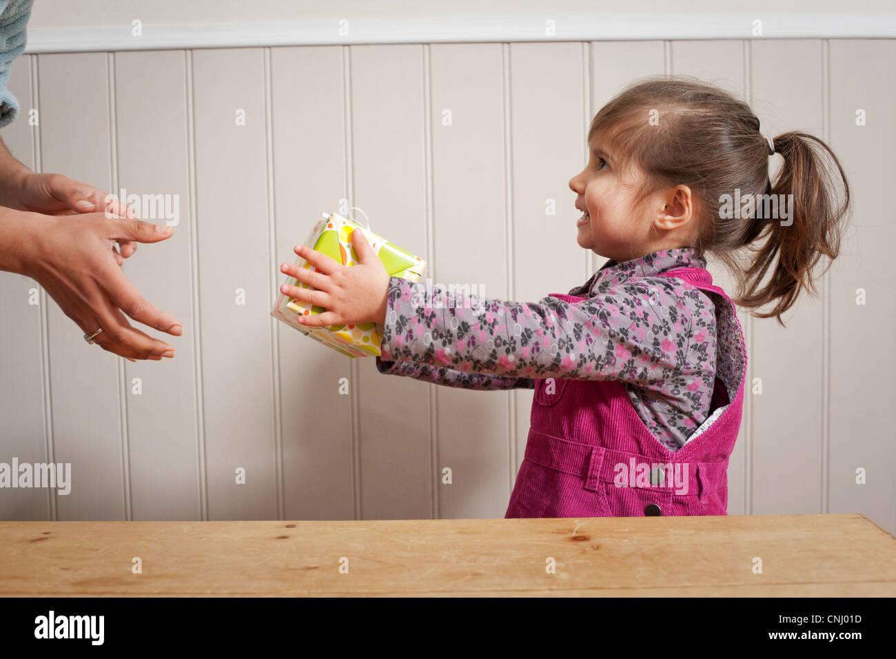 Little Girl dando un regalo para adultos Imagen De Stock