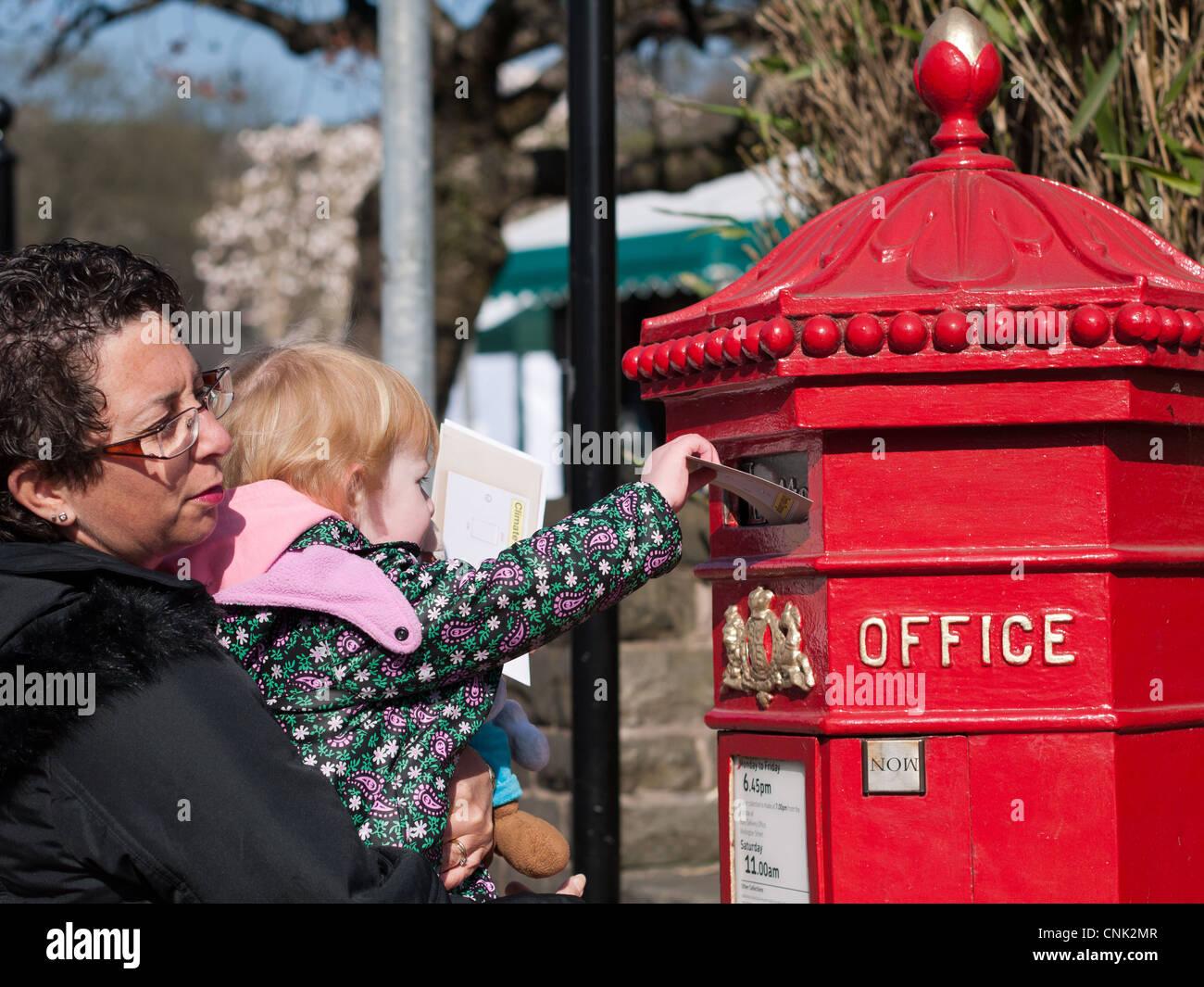 Madre e hija enviar cartas en la casilla postal tradicional Imagen De Stock