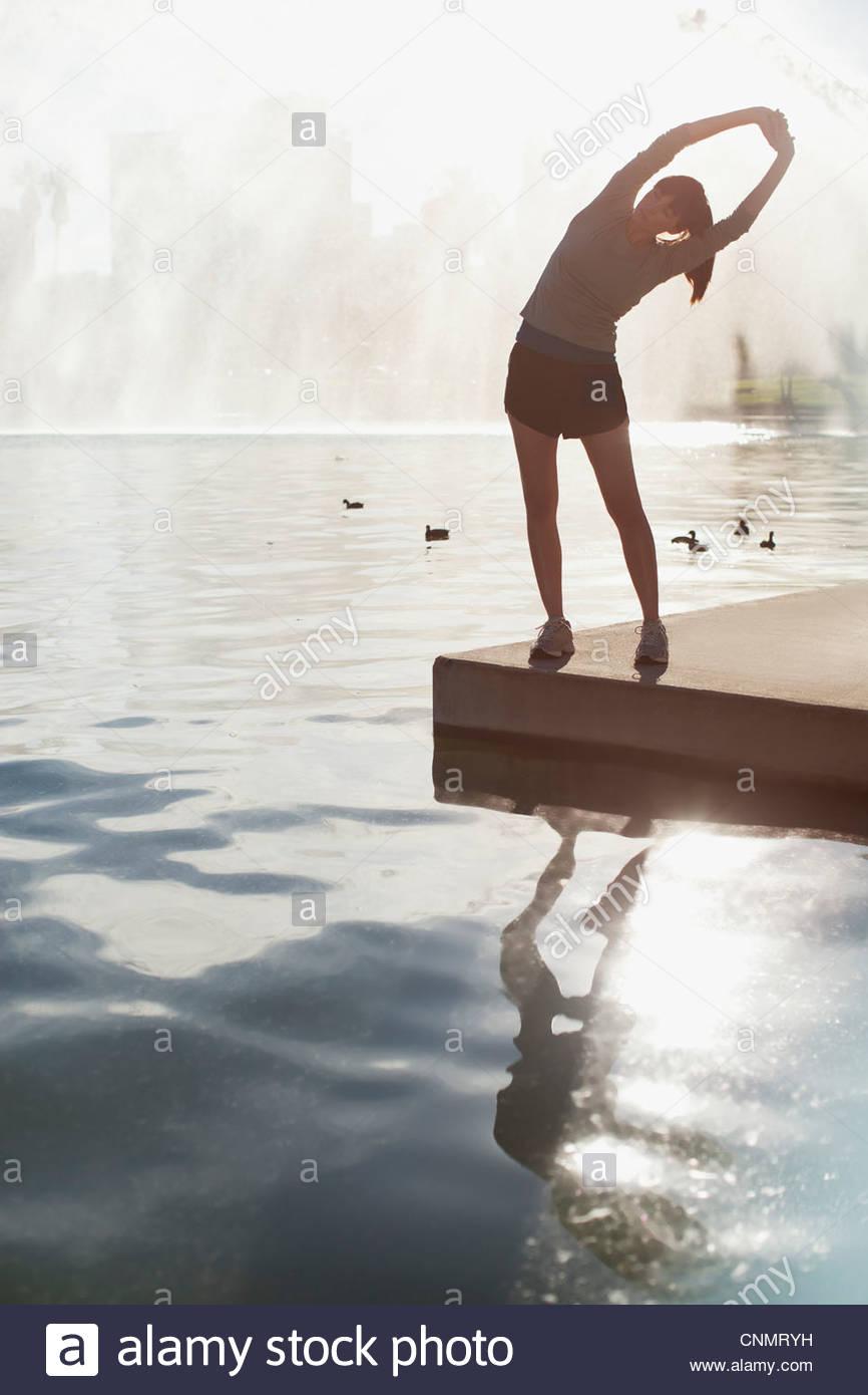 Estiramiento de la mujer aún por el lago Imagen De Stock