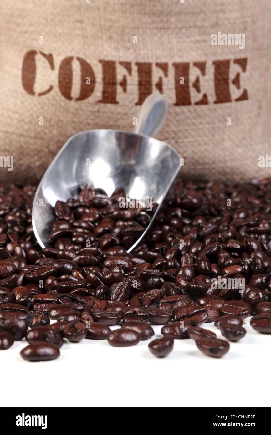 Foto de granos de café tostado fresco con una cuchara y sacos de arpillera. Foto de stock