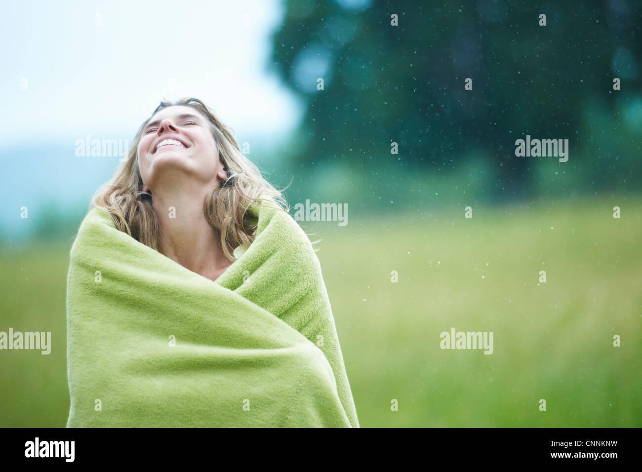 Mujer envuelta en una manta en el exterior Foto de stock