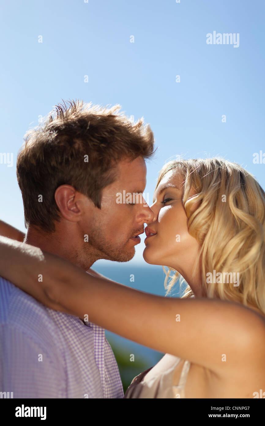 Pareja sonriente besos al aire libre Imagen De Stock