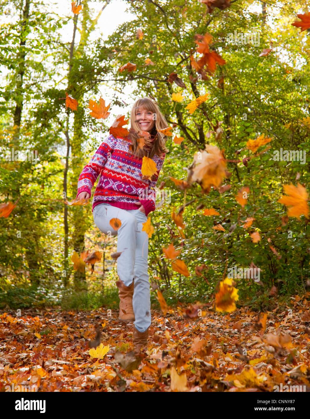 Mujer jugando en hojas caer Foto de stock