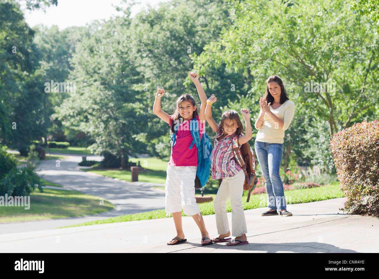 Madre y sus hijas caminando a casa de la escuela Foto de stock