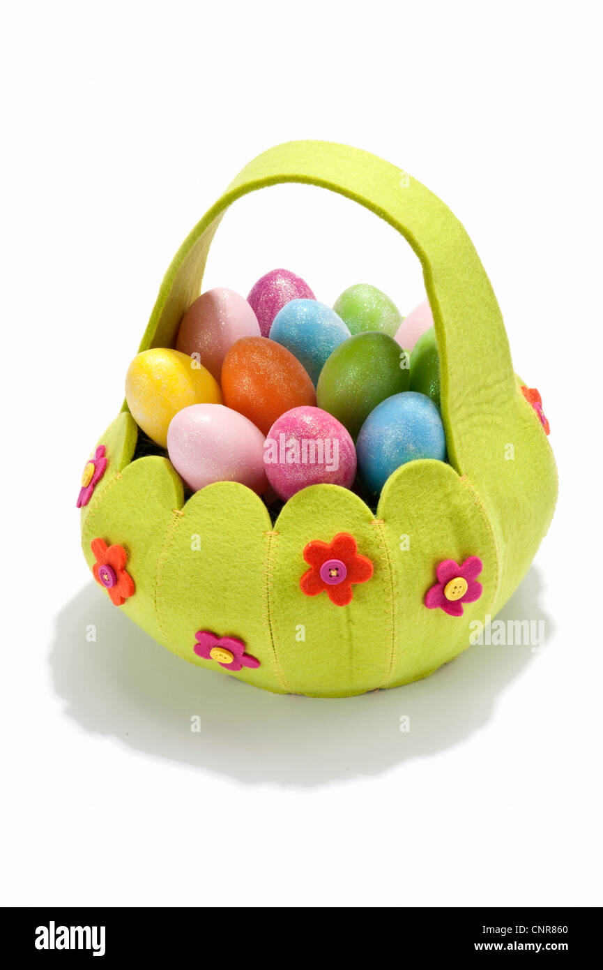 Una canasta llena de huevos coloreados Foto de stock