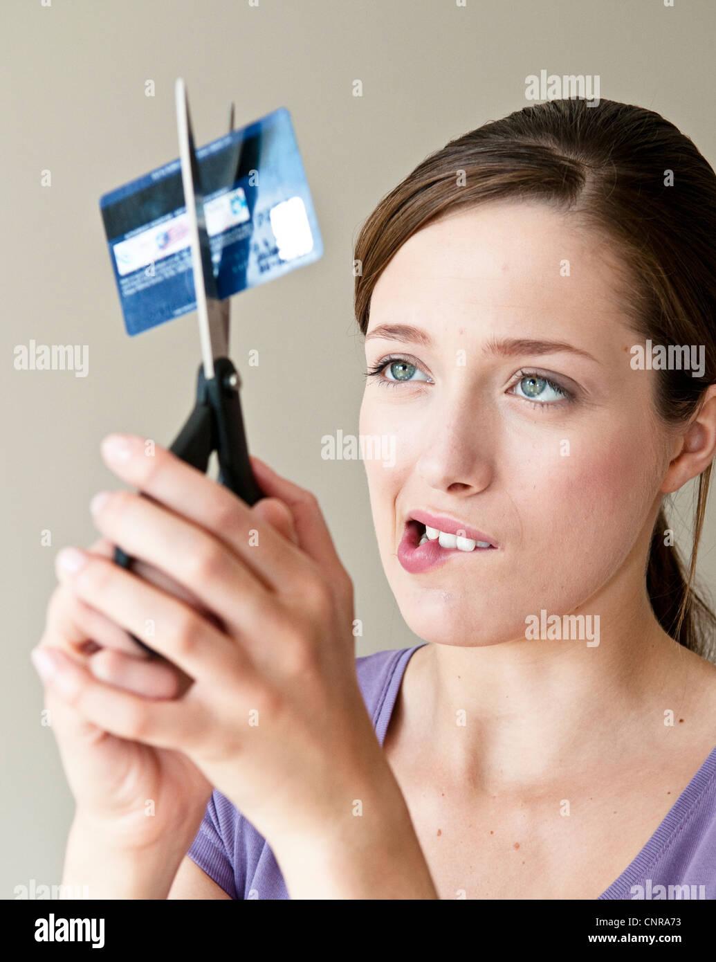 Mujer cortando tarjeta de crédito Foto de stock