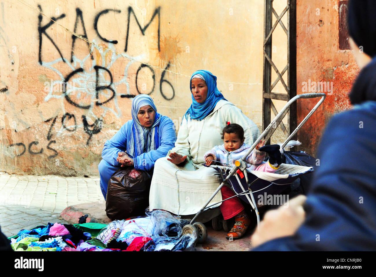 Las mujeres con hijos vender unos pocos elementos en la calle, en el casco antiguo de la Medina de Marrakech, Marruecos Imagen De Stock