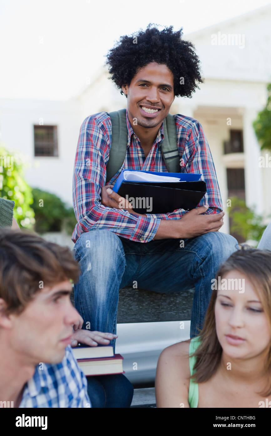 Hombre sentado con sus compañeros en el campus Foto de stock