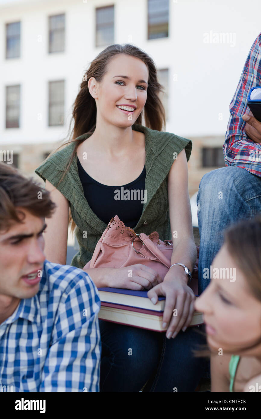 Mujer sentada con colegas en el campus Foto de stock