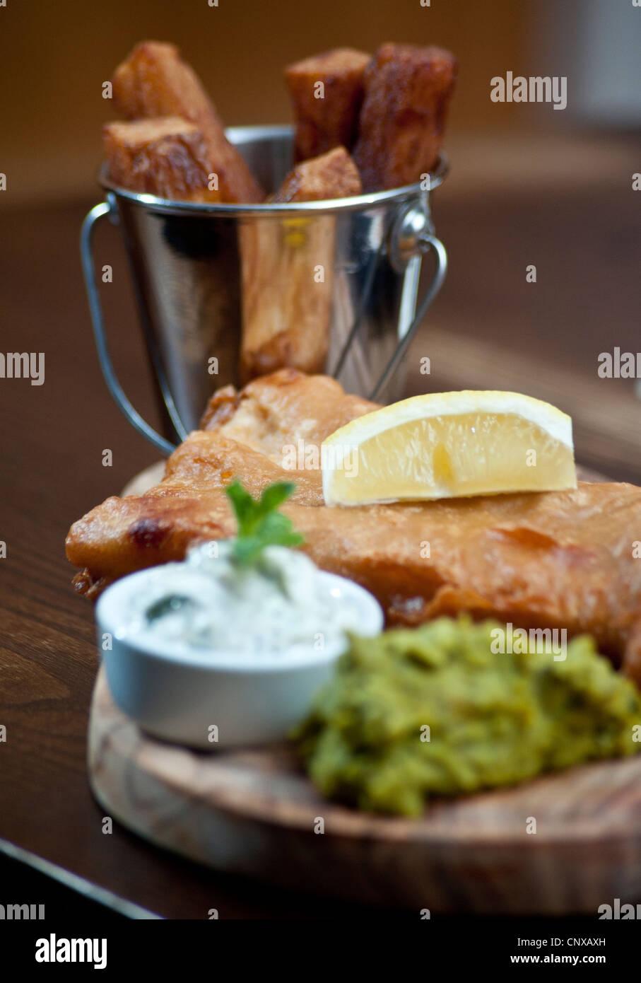 Imagen por Darren enfriar el pescado con patatas fritas y puré de guisantes y salsa tártara, servido en Imagen De Stock