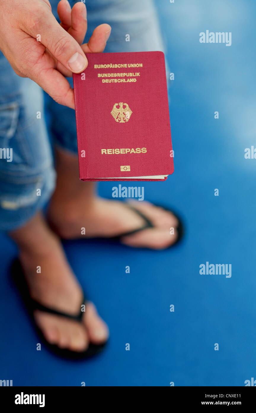 Detalle de un hombre sosteniendo un pasaporte alemán Imagen De Stock