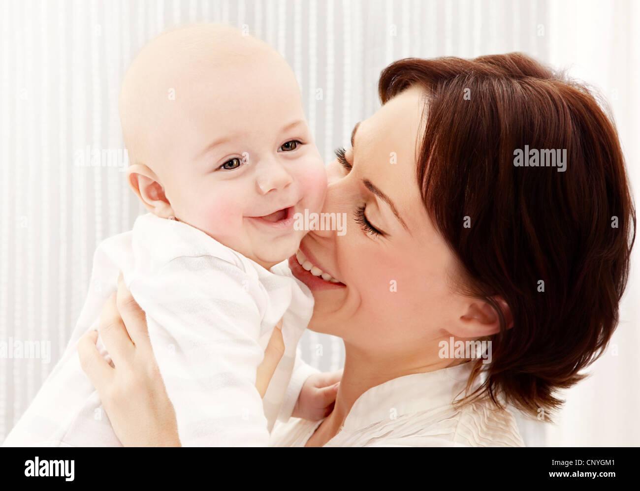 Feliz joven madre sosteniendo un Baby Boy, jugando riendo divirtiéndose, concepto de familia saludable Imagen De Stock