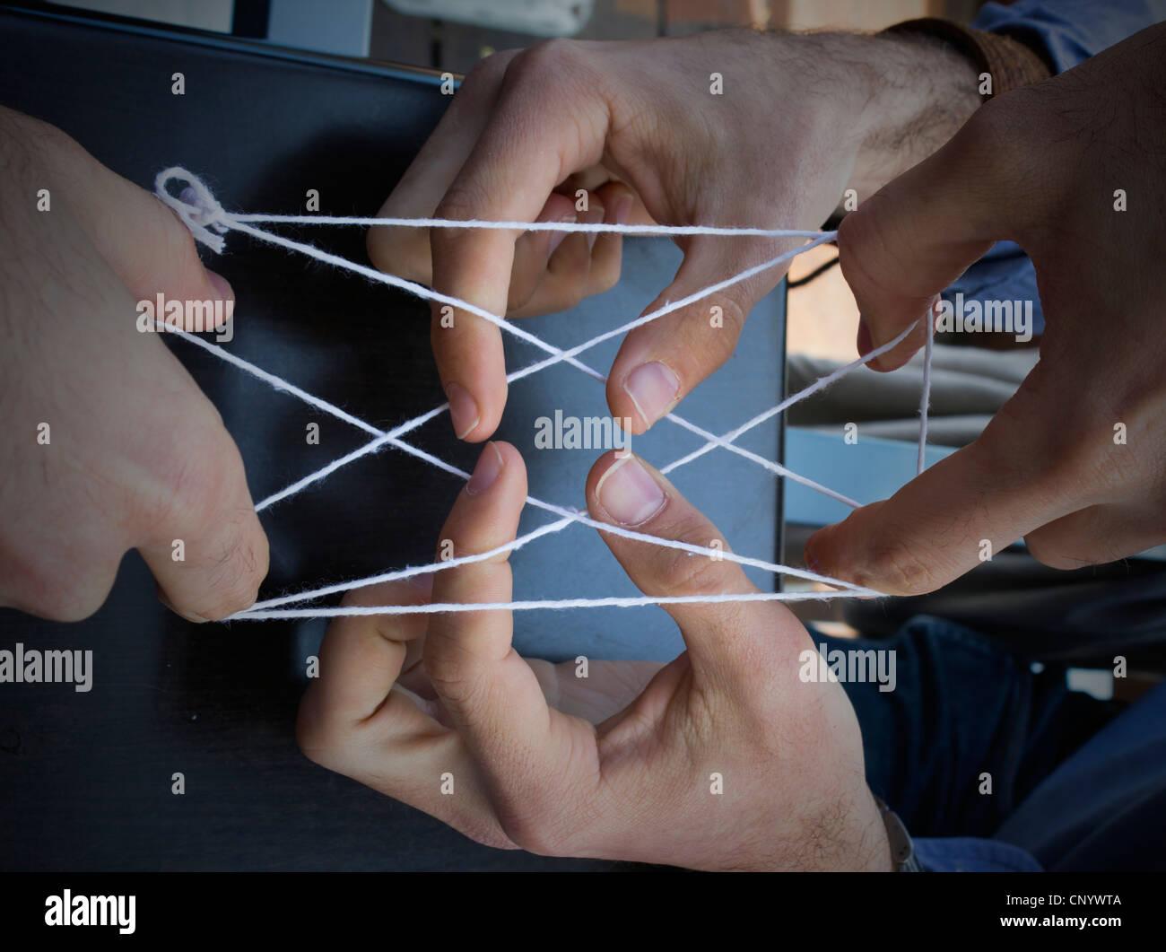 Manos jugar cat's cradle con un trozo de cadena Imagen De Stock
