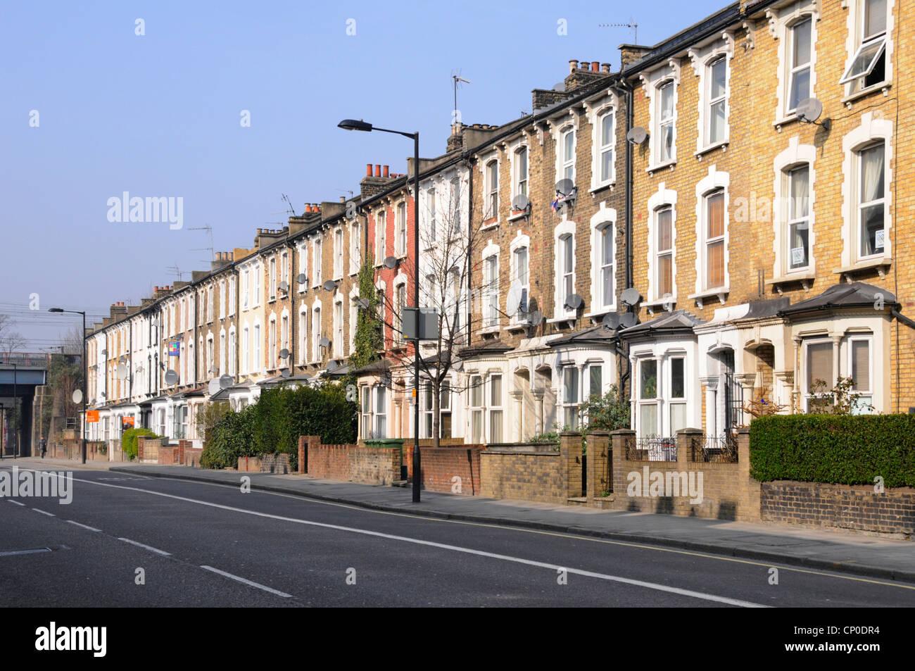 Larga fila de antiguas viviendas adosadas de tres pisos y apartamentos sin coches aparcados en Hackney Londres cerca Imagen De Stock