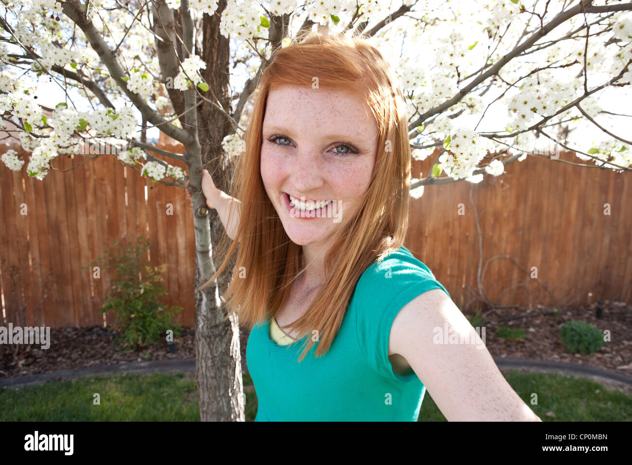 Quince años chica sonriente y sosteniendo a white Pear Tree están floreciendo. Imagen De Stock