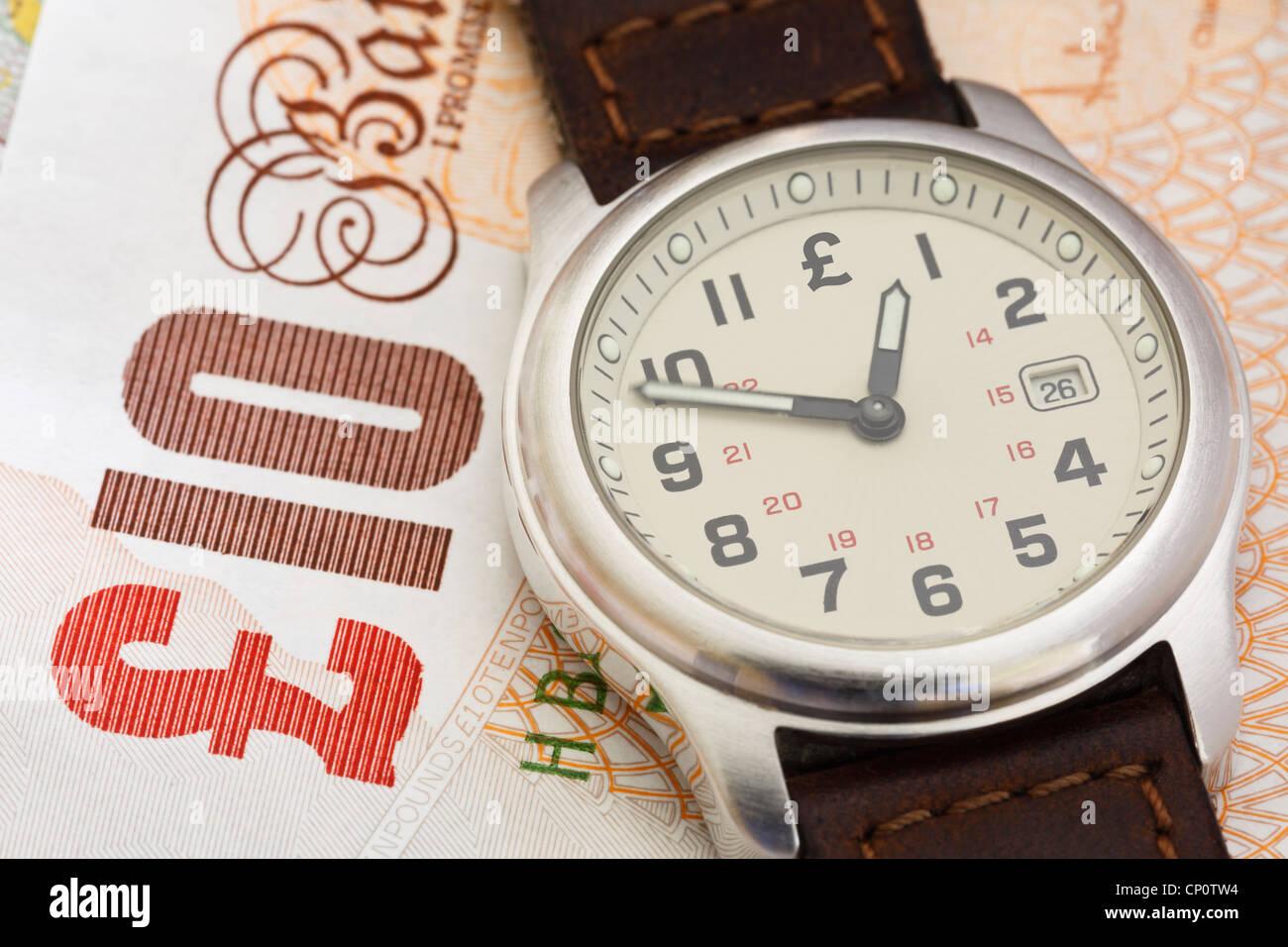 Reloj de pulsera reloj sobre una nota de diez libras esterlinas GBP para ilustrar el tiempo de poner dinero en concepto de pensión. Inglaterra, Reino Unido, Gran Bretaña Foto de stock