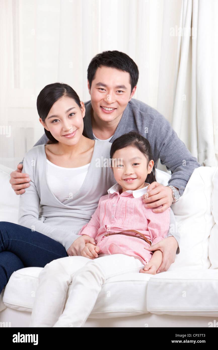Familia joven sentado en el sofá Imagen De Stock