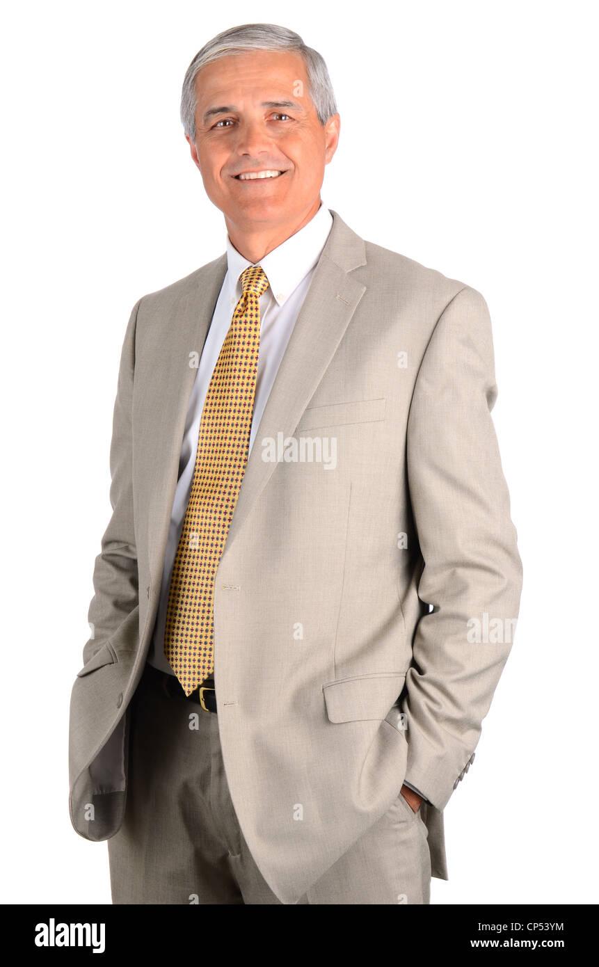 Hombre de negocios de edad media sonriente con las manos en los bolsillos. Tres cuartos sobre un fondo blanco. Imagen De Stock
