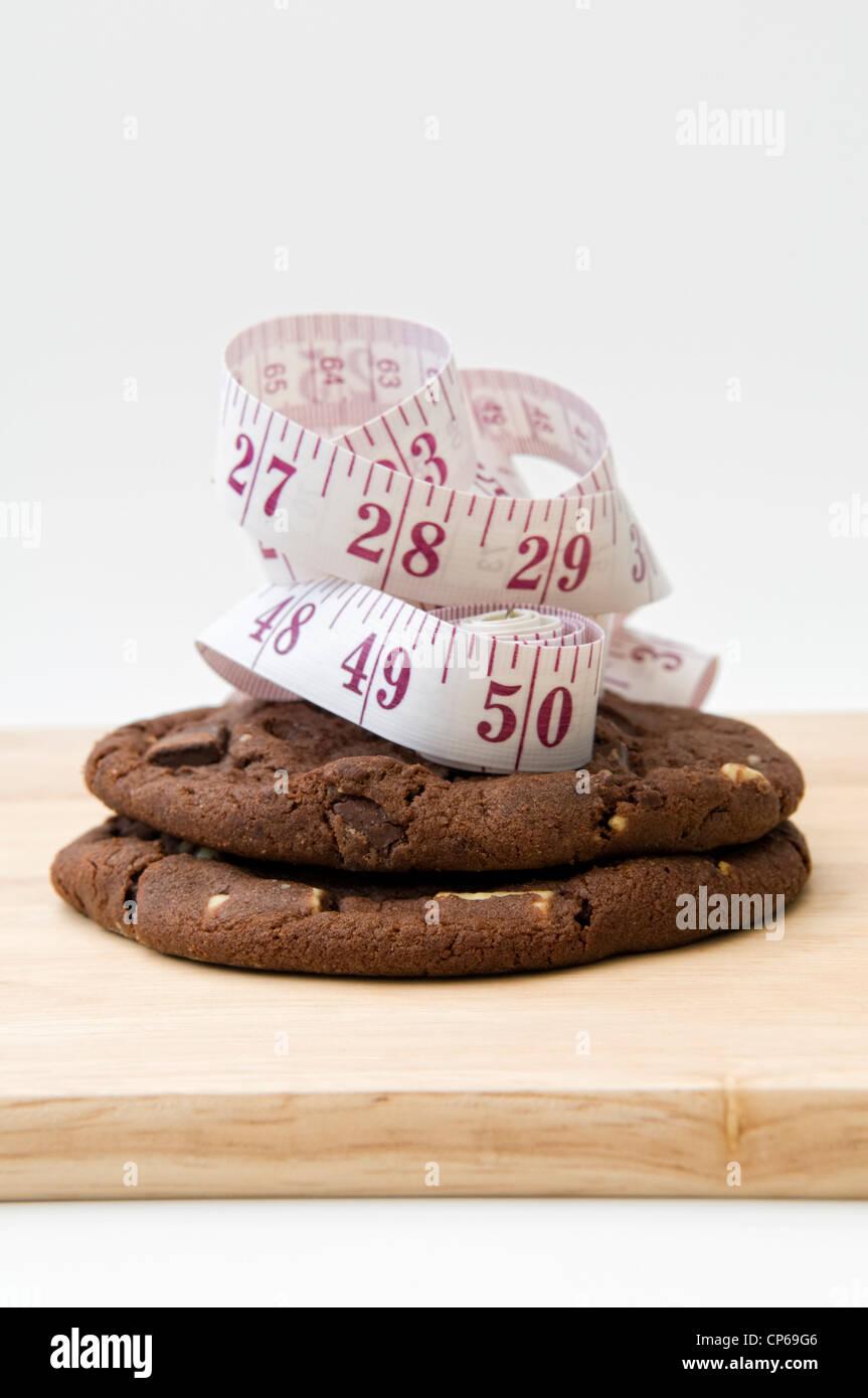 Las cookies sobre una tabla de cortar con cinta de medir, representando el concepto que comer galletas se amontonan Imagen De Stock