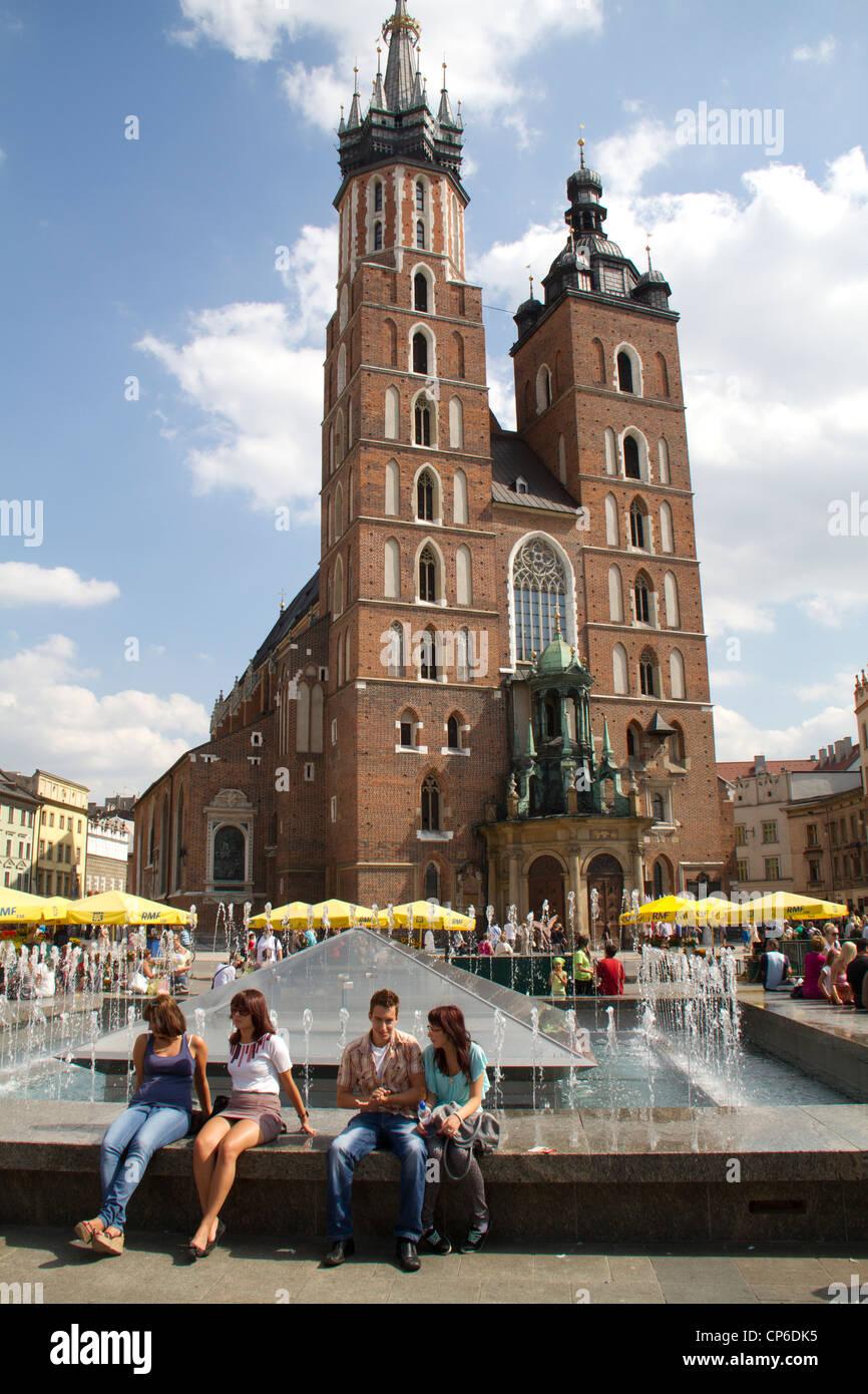 Gente sentada junto a la fuente en la plaza del mercado de Cracovia, Polonia Imagen De Stock