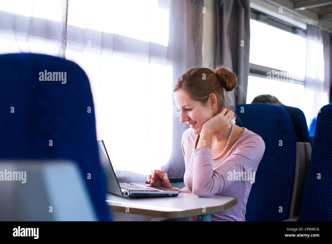 Mujer joven con su ordenador portátil mientras el tren (DOF superficial; imagen en tonos de color) Imagen De Stock