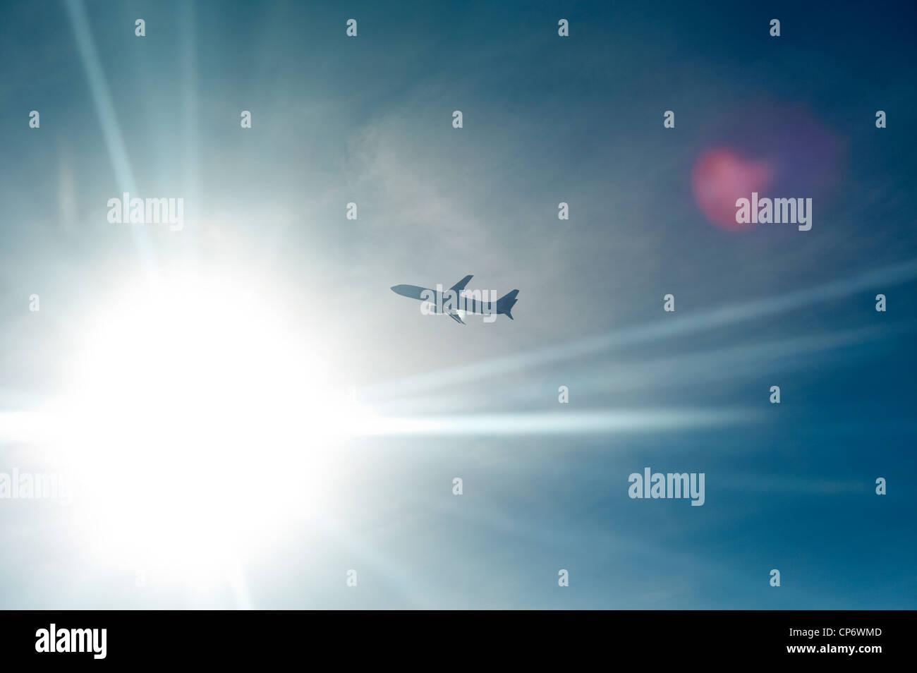 Un avión retroiluminada por el sol en el aire Imagen De Stock