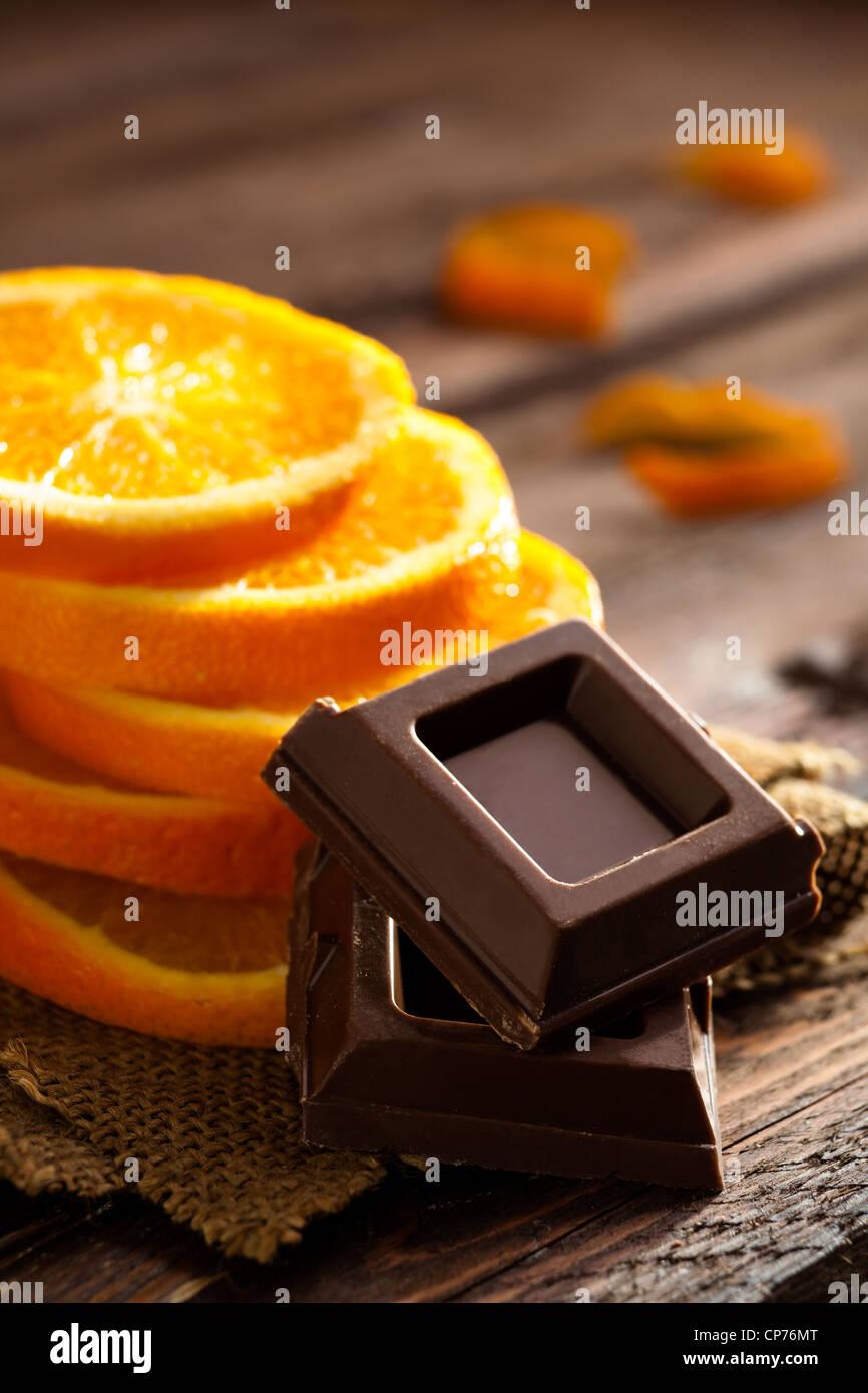 Los cuadrados de chocolate con las rodajas de naranja sobre el Yute y madera Imagen De Stock