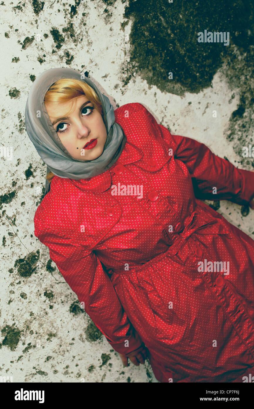Mujer joven con una elegante bufanda y impermeable en la década de los 60's style Foto de stock