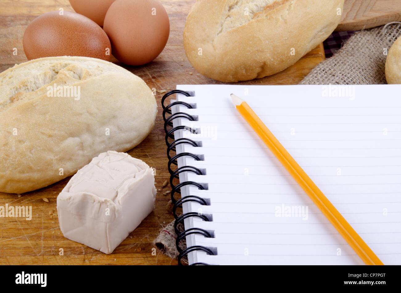 Rollo francés y un cuaderno de notas con lápiz Foto de stock