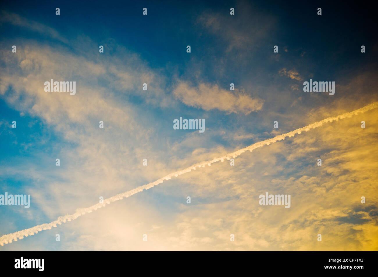 Las estelas de condensación de chorro de aerolíneas comerciales a través de un claro atardecer Atardecer cielo azul Foto de stock