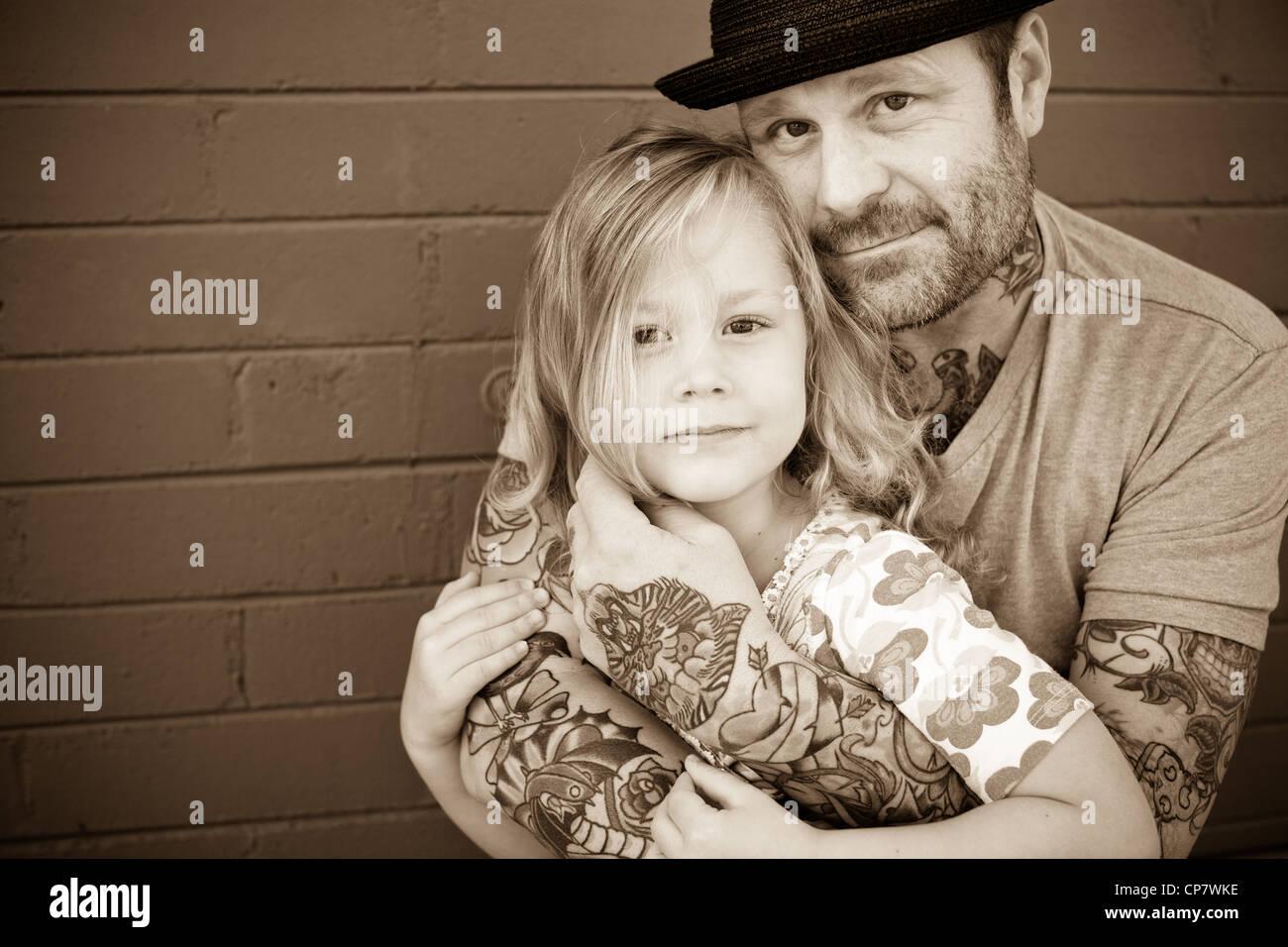 El padre tiene a su hija de cinco años y mira a la cámara. Imagen De Stock
