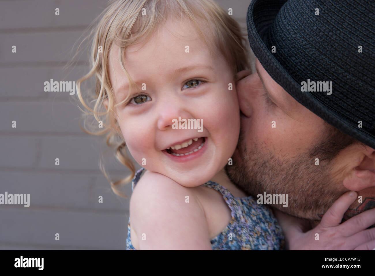 Adorable niña de dos años se ríe como su papá besa a su cuello, cerca. Imagen De Stock