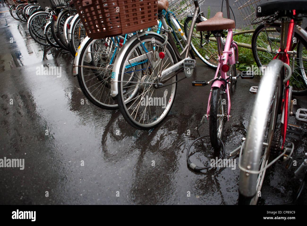 Bicicletas aparcado en un día lluvioso en Tokio, Japón. Imagen De Stock
