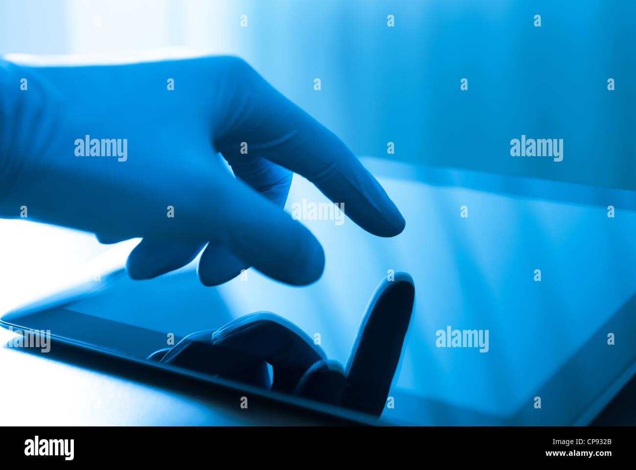 Mano en Guante azul tocar tablet digital moderna. Concepto de imagen médica o tema de investigación. Foto de stock