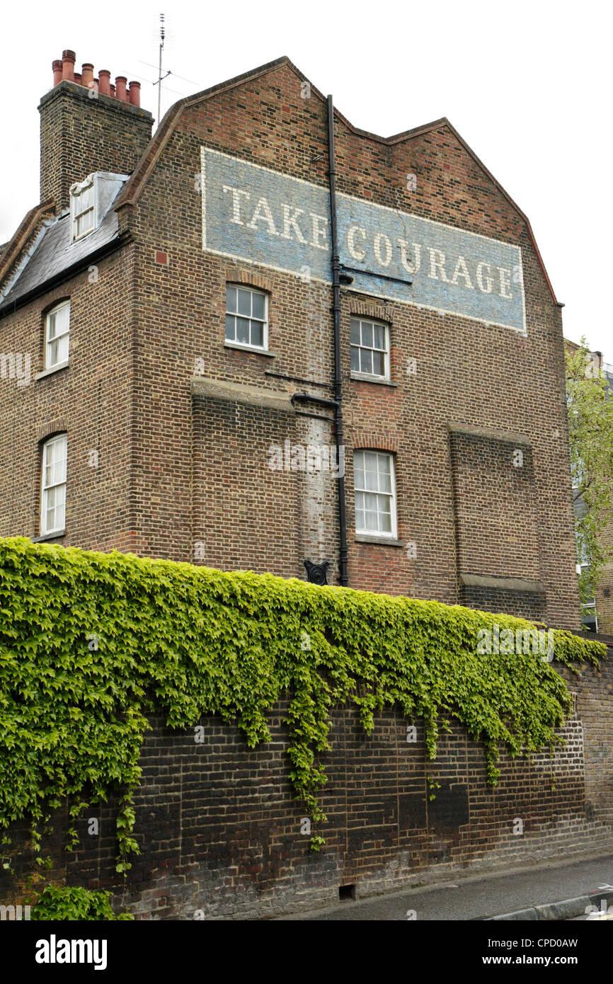 """Pintado """"tomar coraje' anuncios de cerveza en el lateral del edificio, Londres, Reino Unido. Foto de stock"""