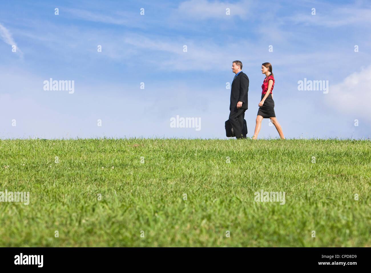 Caucasian co-trabajadores caminando a través de césped Foto de stock