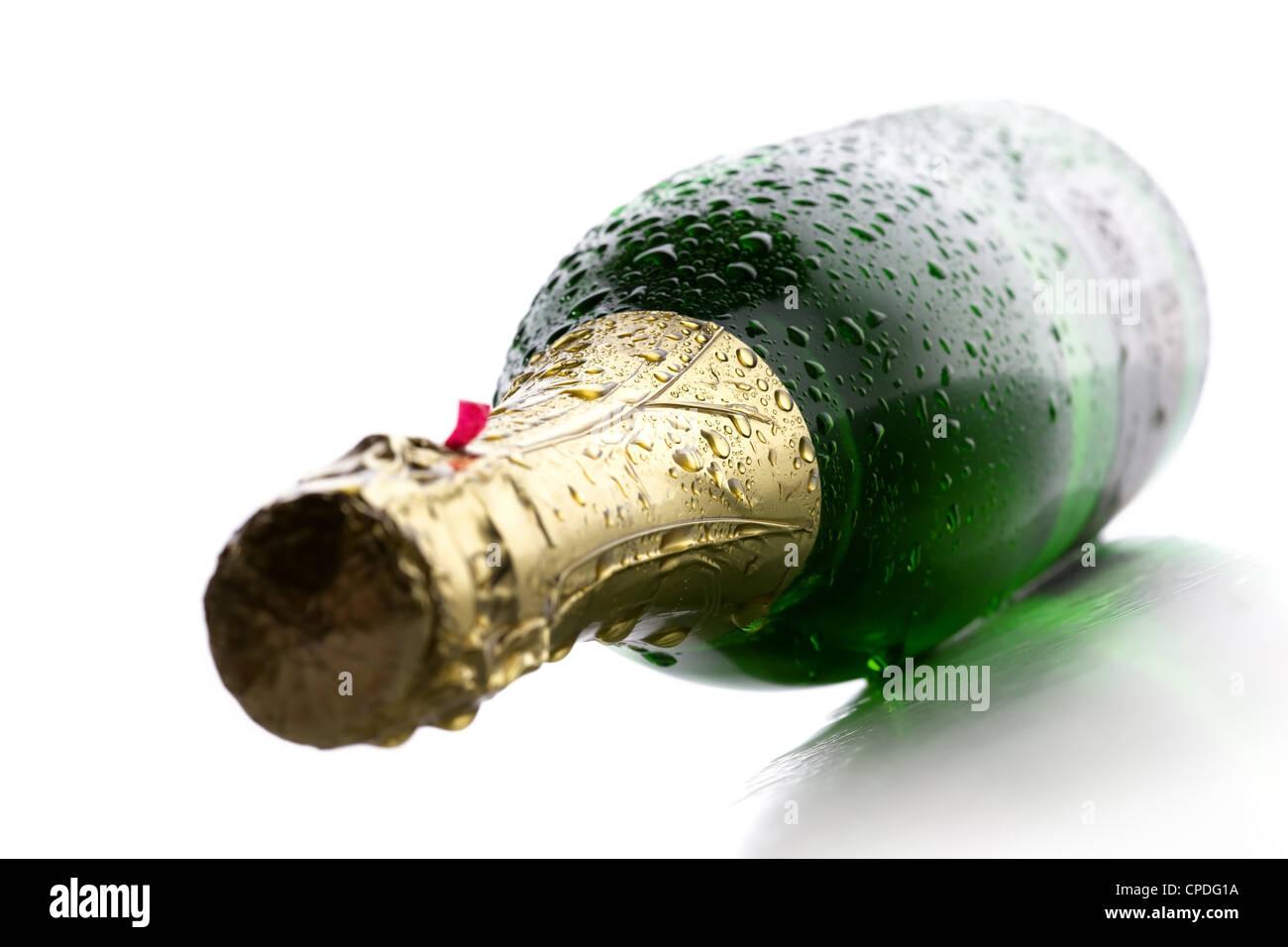 Botella de champaña fría y mojada vino sobre fondo blanco. Imagen De Stock