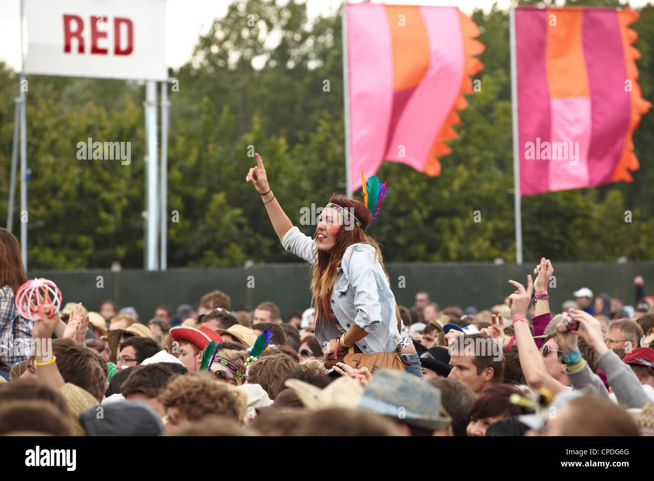 Niña en un festival de música en los hombros de la multitud aclamando Imagen De Stock