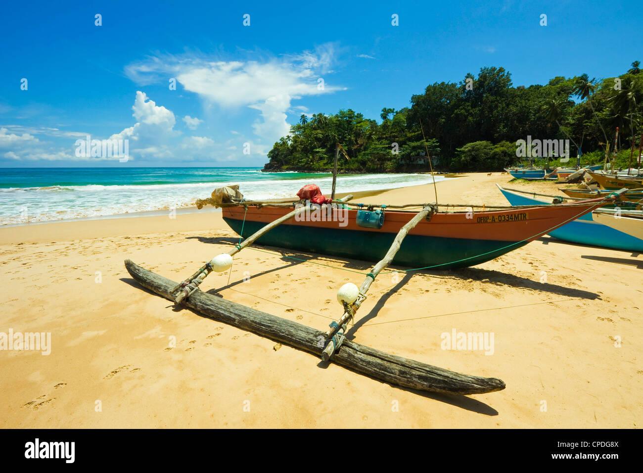 Outrigger botes de pesca en este tranquilo refugio costa sur playa, Talalla, cerca de Matara, la provincia meridional de Sri Lanka, Asia Foto de stock