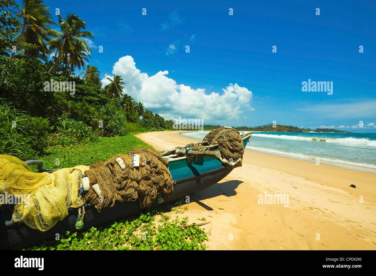 Outrigger botes de pesca y redes en este tranquilo refugio costa sur playa, Talalla, cerca de Matara, la provincia meridional de Sri Lanka Foto de stock