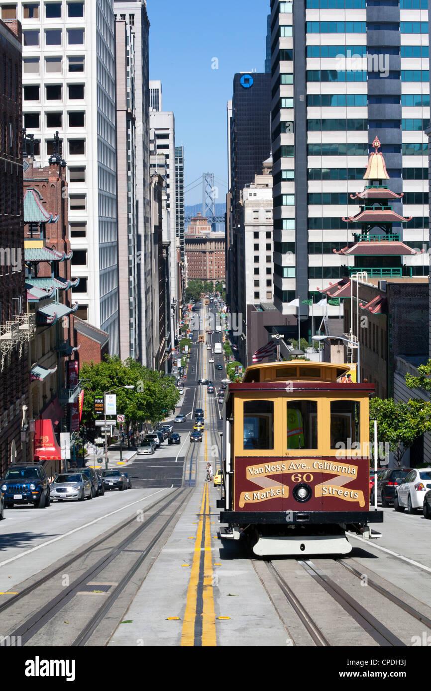 Teleférico cruzando la calle California con telón de fondo el puente de la Bahía de San Francisco, Imagen De Stock