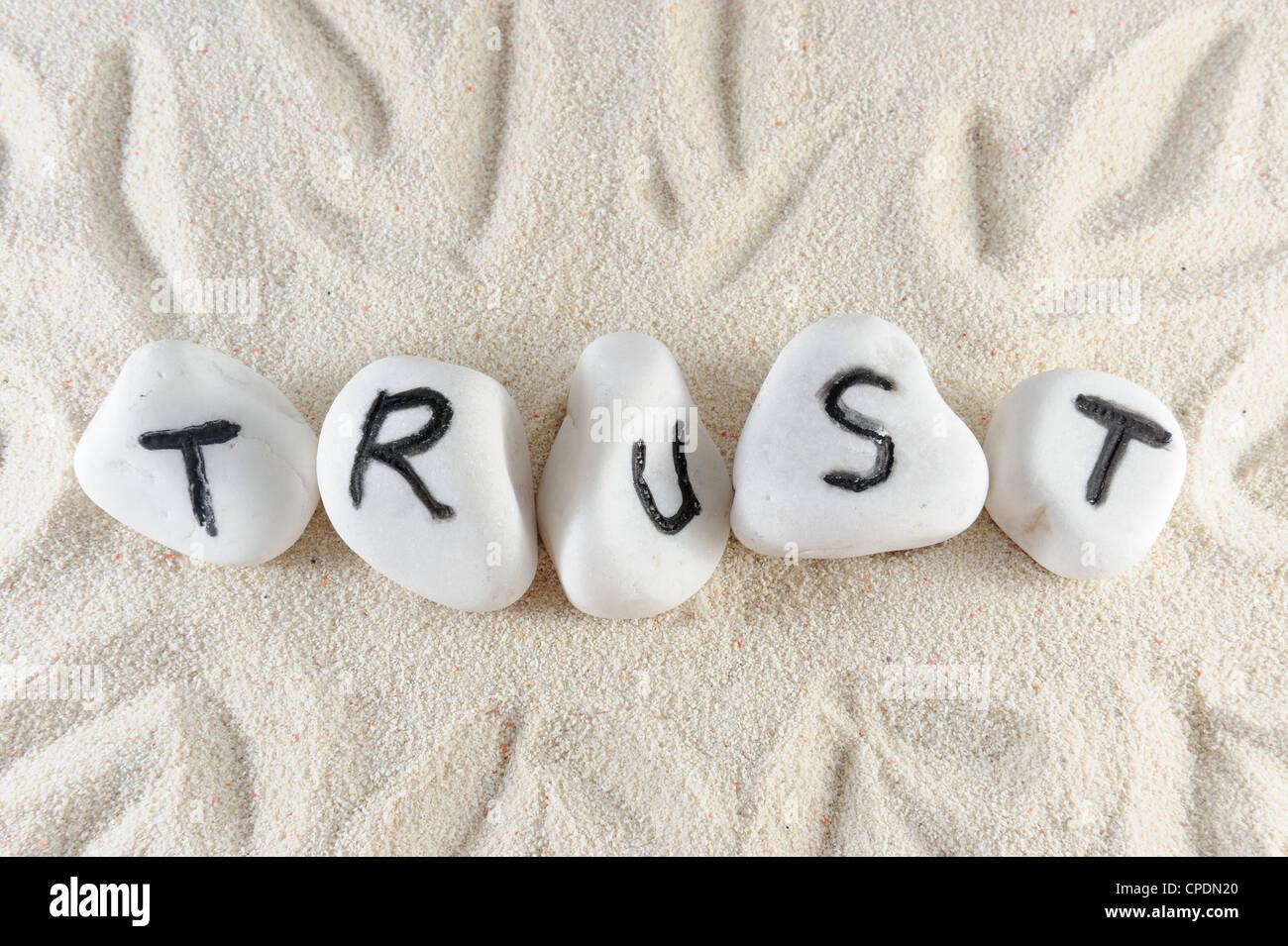 Palabra de confianza en el grupo de piedras en la arena Imagen De Stock