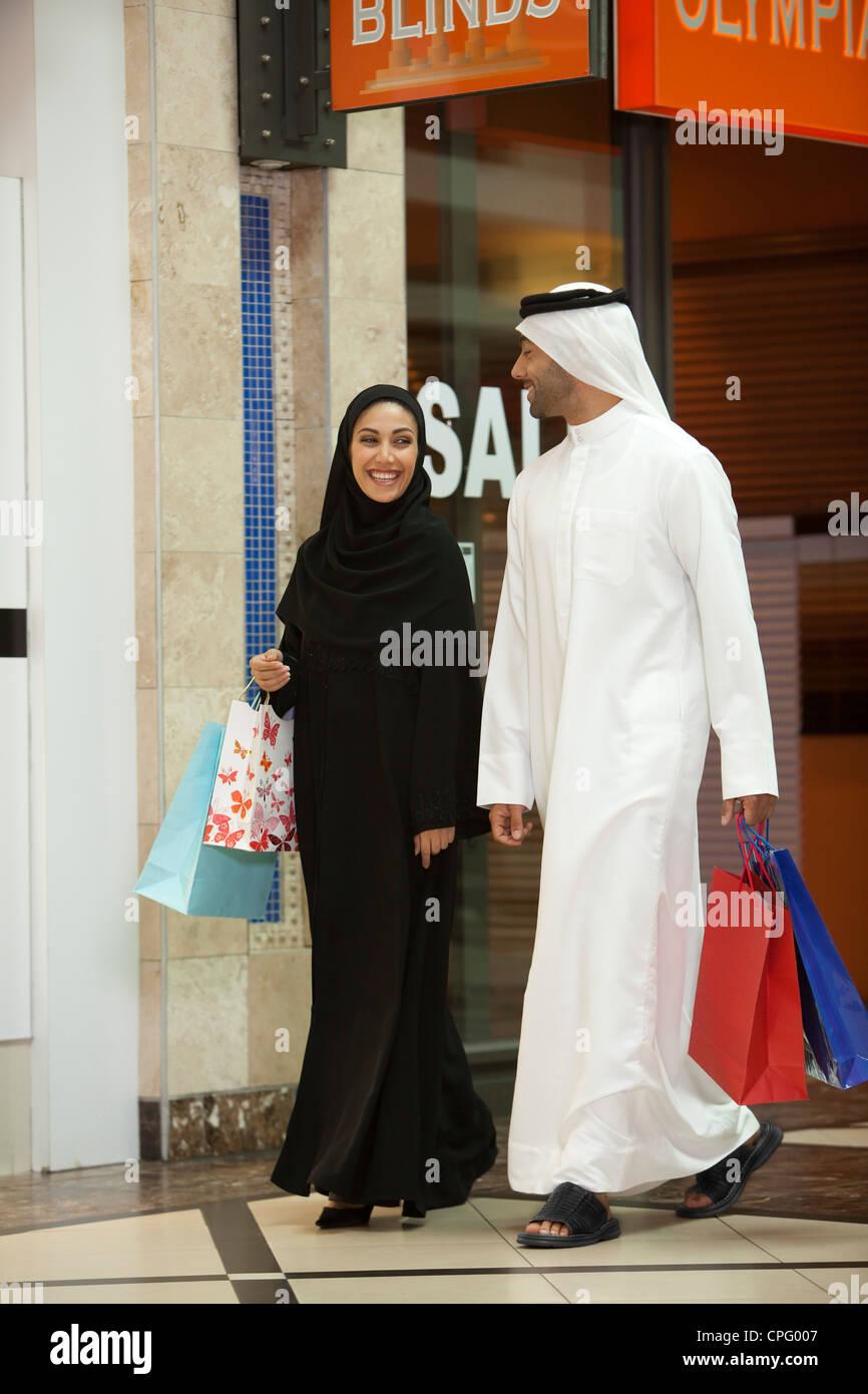 Pareja árabe con bolsas de compras caminando en el mall. Foto de stock