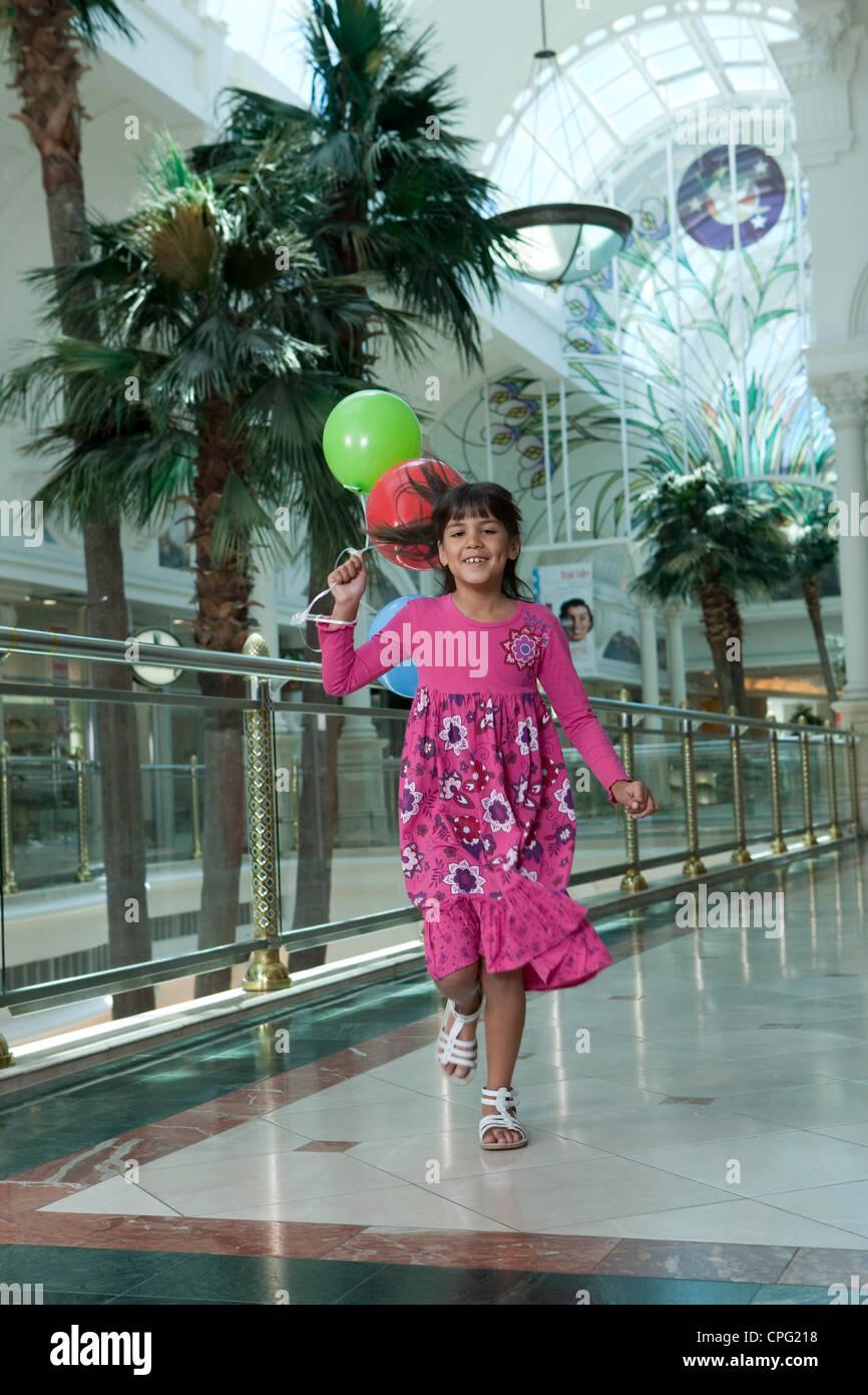Chica corriendo con globos en el centro comercial. Imagen De Stock